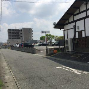 横の道を右折すると裏に駐車場の入り口があります。奥に見える6階建てのマンションです。